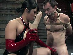 Dragonlily is a sexy mistress and now it's time for her to take care of her slave. She has tied him up in rope and he's down on his knees. He mouth is wide open in clamps and she shoves a huge dildo down his throat.