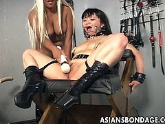 This blonde mom loves to play with her brunette Asian chick. She tied her up with her thighs spread, opened her mouth and rubbed her pussy with a vibrator. After she rubbed that bald pussy the blonde uses a dildo strapped on a sex machine to fully satisfy the chick.