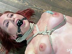 Redhead slut Sophia likes it rough, a bit too rough maybe. She's tied up, laid on the floor and with a ball gag in her mouth. The executor grabs her body firmly and even pinches her nipples. She would like to scream, but that ball gag keeps her silent, as the guy continues the warm up for what's about to happen.