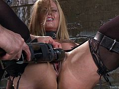 This blonde chick is tied to a wooden plank and her legs are spread open with leather straps. She is about to experience some intense orgasmic pleasure as her master pleases her with a vibrator attached to a long stick.