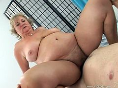 Well-endowed blonde granny is playing dirty games with some man in a bedroom. They fondle each other and then bang in cowgirl and other positions.