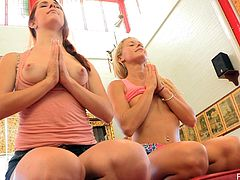 These two sexy girls do some yoga in some very short shorts before stripping naked and passionately kissing each other.