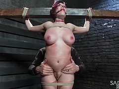 She thought she's a bad ass punk slut, but our executor knows how to handle sluts like she is. He crucified her and now, that she's all tied up on that wood structure, he does his ways with her. First, the guy plays with her pussy, whips her boobs and then, gropes them. Now she's ready for the punishment!