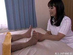 Nasty Japanese milf Hana Nonoka wearing a nurse uniform is getting naughty with some dude in a hospital ward. She massages the man's feet and then decides to taste his boner.