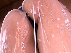 Horny Japanese chick wearing a swimsuit is playing dirty games in a sauna. She pours water on her butt and demonstrates it for the camera and then drills her pussy with a realistic toy.
