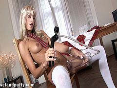 A beautiful blonde girl in a sexy school uniform pumps her pussy with a special devices. Erica also toys her incredible pussy with a glass dildo lying on a table.
