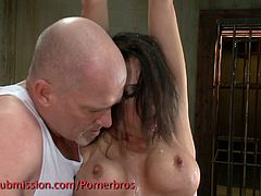 This submissive brunette has her hands tied up together and hanging from the ceiling. Her master makes her swallow his big cock and whips her.