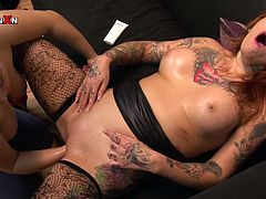 Lustful red haired tramp with tattooed body and in black stockings lies on back with her legs spread apart and gets her wet kitty fisted by that brutal slutty woman. Take a look at that hot fuck in Porn XN sex clip!