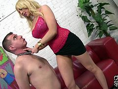 Sexy big-breasted blonde Christie Stevens wearing a top and a miniskirt is having fun with some man indoors. She puts a dog collar on his neck and plays BDSM games with him.