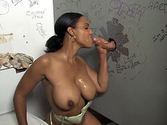 Captivating black chick Samone Taylor shows her terrific big tits and kneads them. Then she squats in front of a hole in the wall and sucks a weiner sticking out of it.