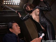 The sex slave is dressed in latex and has her arms bound to the ceiling with some chain. She is dangling their as her master uses a vibrator on her pussy. He lets her down so she can suck cock, and she sucks so many cocks!