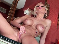 Amazingly hot blonde chick with fake tits masturbates sitting on a chest of drawers. Lacey rubs her pussy lips and fingers.