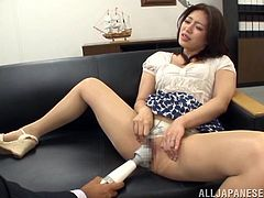 Check this Asian brunette, with big knockers wearing cute panties, while she gets her pussy stimulated sitting on a couch and moans stridently.