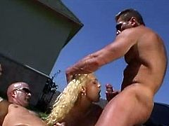 Slutty blonde Trina Michaels is getting naughty with two muscular dudes outdoors. She sucks and deepthroats their big cocks and then gets double penetrated.