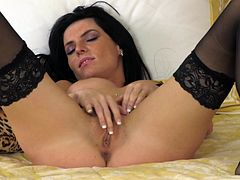 A sexy brunette chick in sexy lingerie and stockings masturbates lying on a bed. This cute babe rubs her clit and toys the pussy with a pink dildo.