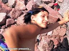 Witness this video where a short haired brunette, with big boobs wearing a bikini, gets fucked hard on the beach and moans loudly.