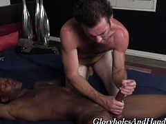 They're as opposite as ebony and ivory, but they both agree in the power of hand jobs. Watch this man go down on his knees for that huge black cock.