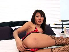 Have a good time watching this Asian brunette, with a nice ass wearing fishnet stockings, while she gets her pussy destroyed and moans loudly.