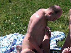 On the grass is where cutie spreads the legs to engulf two senior cocks in a slutty trio adventure