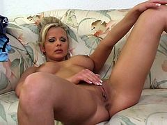 Sizzling blonde milf Adrianna Russo is having fun on a sofa. She spreads her legs wide open and entertains herself by masturbating her coochie.