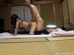 Get a hard dick watching this Asian brunette, with a nice ass wearing socks, whiles he gets plowed hard by an older dude over a bed.