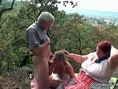 A sexy blonde and a fat granny give head to an old man. They both have huge boobs and they are both sucking cock. He prepares to fuck the young chick from behind.