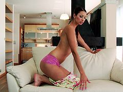 A slim and tall brunette girl takes off her dress and lies down on a sofa. Kitty plays with her shaved pussy using both hands.