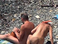 Hidden cam pleases voyeur's desires by spying one nude hottie enjoying the sun at the beach