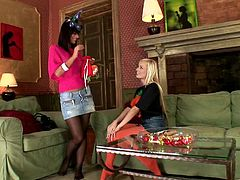 Black Angelica and Szofya Cox wearing stockings are playing lesbian games in the living room. They lick each other's feet ardently and show their shaved coochies to each other.