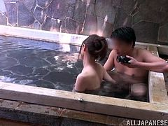 A slim Japanese girl with a pretty face gives a handjob to some guy in an outdoor bath. This hottie also sucks that cock with pleasure.