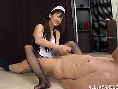 Kinky Japanese chick, wearing a maid uniform, is getting naughty with a guy indoors. She takes his schlong out of his pants and rubs it till it explodes with cum.