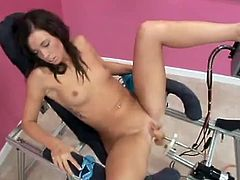 Slim and hot girl sits on a special chair with her legs wide opened. She toys herself with a vibrator while a fucking machine drills her pussy.