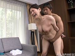 Have fun watching this Asian MILF, with a nice ass wearing panties, while she gets nailed hard over a couch and moans like a naughty cougar.
