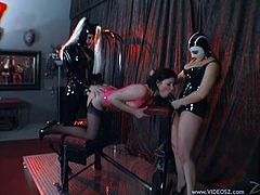 These three babes wear masks, latex and strapons as they tie up one of the girls and fuck her hard in this kinky dungeon.