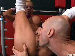 A beautiful blonde cougar with long hair, massive fake tits and a shaved pussy enjoys a mind-blowing cowgirl style fuck in a gym.
