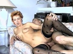 A beautiful cougar with short red hair, petite natural tits and a shaved pussy enjoys a hardcore fuck in her living room.