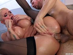 An oiled-up pornstar with short blonde hair, massive fake tits and a fantastic body enjoys a hardcore cowgirl style fuck in her garden.