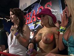 A sexy blonde chick is getting naughty at a party. She flashes her big beautifl tits and allows some nasty girls to lick them.