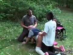 These two young dudes take a granny out of her wheelchair and fuck her in the backyard. They are rough with her and force her to keep her eyes open when they give her facials.
