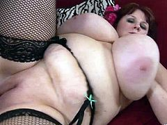Have fun watching this brunette BBW, with gigantic bazookas wearing fishnet stockings, while she gets drilled hard over a red couch.