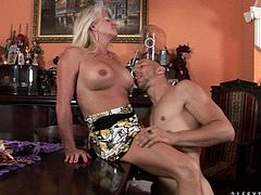Prepare your cock for this blonde mature woman, with big fake jugs wearing a cute dress, while she gets banged hard over a dining table.