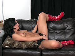 A sizzling brunette babe with long hair, beautiful natural tits and a shaved pussy enjoys playing with a plastic cock on her sofa.
