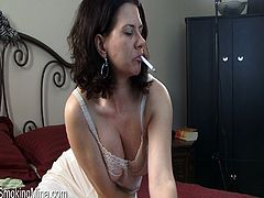 A sizzling hot cougar with long dark hair and a fabulous body enjoys playing with her big natural tits while smoking in her bedroom.