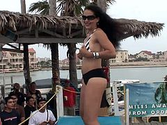 A few hot girls, wearing bikinis, are getting naughty during an outdoor party. The come out on the stage and begin to shake their butts and strip.