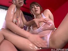 These two busty Japanese girls oil up their great tits then suck and stroke this guy until he explodes all over their big tits.