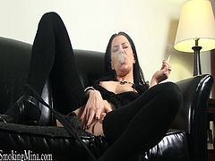 This sexy cougar relaxes on the couch and indulges in her fetish when she enjoys a cigarette while rubbing her shaved pussy.