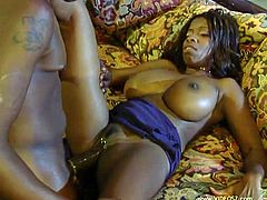 A sizzling ebony-skinned pornstar with long hair, huge fake tits and a hot ass enjoys licking and sucking a stranger's massive cock on her sofa.