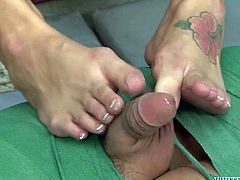 Lusty brunette whore with big tits presents nice foot job to her man