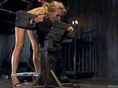Blonde babe Emma is bent over and secured in a bondage device. She can't do nothing about it but to endure the shame and punishment she receives. Her panties where pulled down, a metal hook was inserted in her tight ass hole and now the executor plays with a vibrator on her sweet pussy. curious what's next?