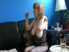 Beautiful matured cougar with big natural tits in black fishnets smokes passionately while relaxing on a black sofa in a close up shoot